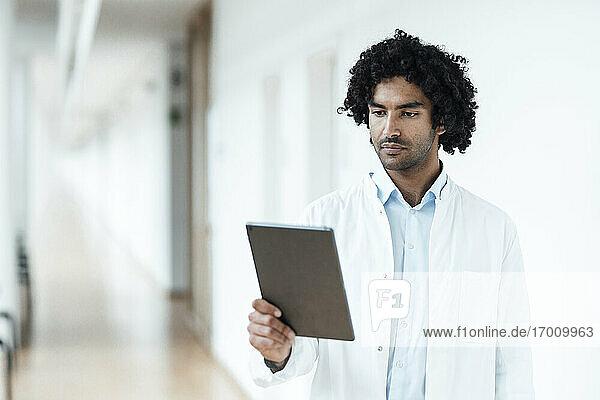 Selbstbewusster junger Arzt  der ein digitales Tablet auf dem Flur eines Krankenhauses benutzt