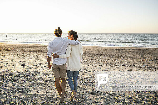 Young couple with arms around walking at beach during sunset