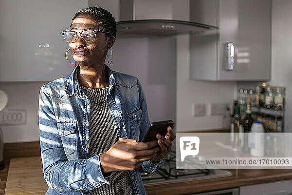 Woman holding smart phone in kitchen