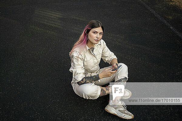 Stilvolle Frau mit Smartphone auf dem Sportplatz Stilvolle Frau mit Smartphone auf dem Sportplatz
