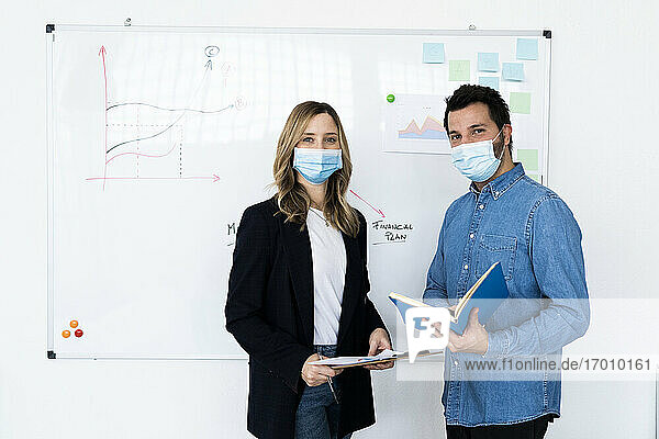 Portrait of business people wearing protective masks in office
