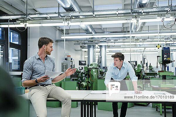 Männliche Kollegen diskutieren in einer Fabrik über einen Bauplan
