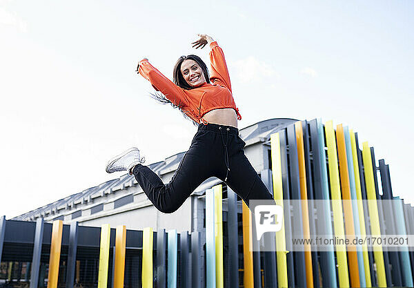 Portrait of beautiful brunette jumping in front of colorful building