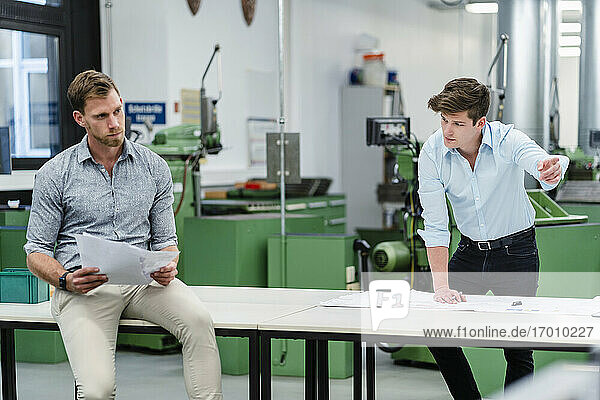 Businessman discussing business strategy with male engineer on desk in factory