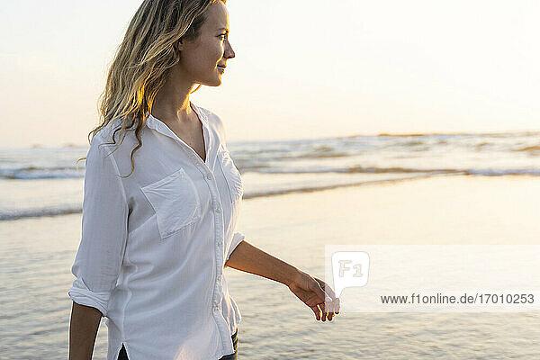 Lächelnde Frau schaut weg  während sie bei Sonnenuntergang am Meer steht Lächelnde Frau schaut weg, während sie bei Sonnenuntergang am Meer steht