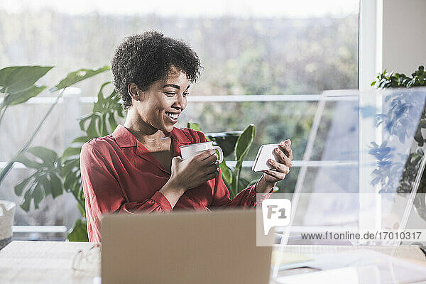 Smiling woman looking at smart phone at desk at home