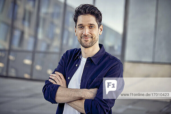 Male entrepreneur standing with arms crossed outdoors