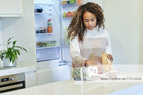 Afro junge Frau organisiert Lebensmittel in der Küche zu Hause Afro junge Frau organisiert Lebensmittel in der Küche zu Hause