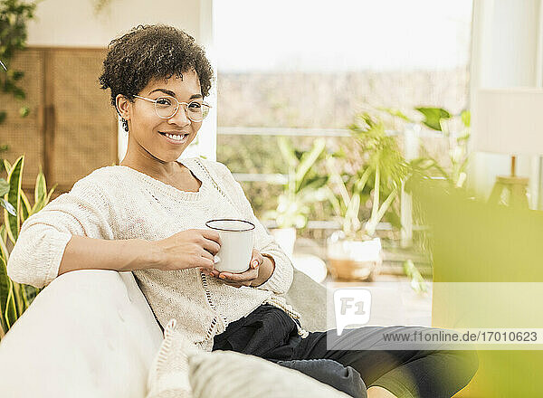 Smiling woman wearing eyeglasses drinking coffee while sitting at home
