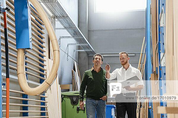 Zwei Zimmerleute unterhalten sich inmitten von Holzbrettern in einer Produktionshalle