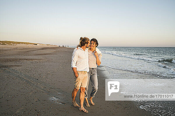 Young couple walking at beach against clear sky during vacation
