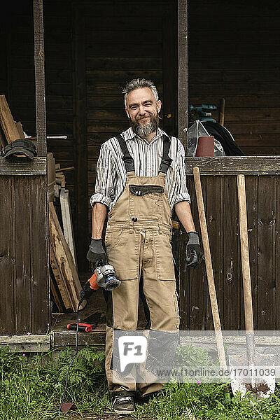 Porträt eines bärtigen Zimmermanns  der mit einer Schleifmaschine in der Hand im Freien steht Porträt eines bärtigen Zimmermanns, der mit einer Schleifmaschine in der Hand im Freien steht