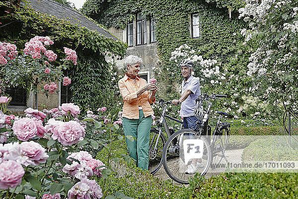 Lächelnde Touristen mit Elektrofahrrädern erkunden den Rosenpark in Dresden  Deutschland Lächelnde Touristen mit Elektrofahrrädern erkunden den Rosenpark in Dresden, Deutschland