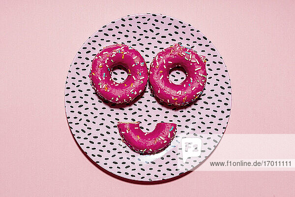 Anthropomorphic face made of plate and pink sugar sprinkled doughnuts