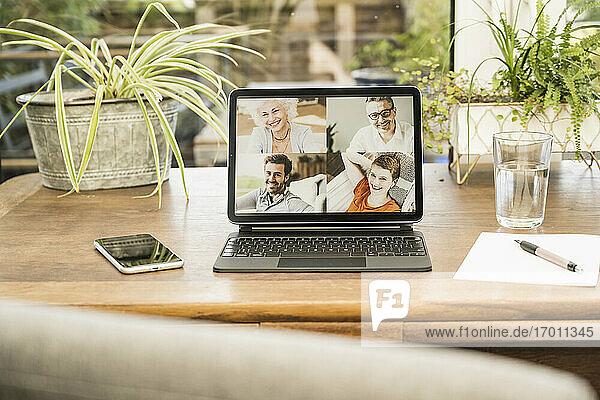 Lächelnder Mann und Frau bei einem Videoanruf über ein digitales Tablet zu Hause Lächelnder Mann und Frau bei einem Videoanruf über ein digitales Tablet zu Hause