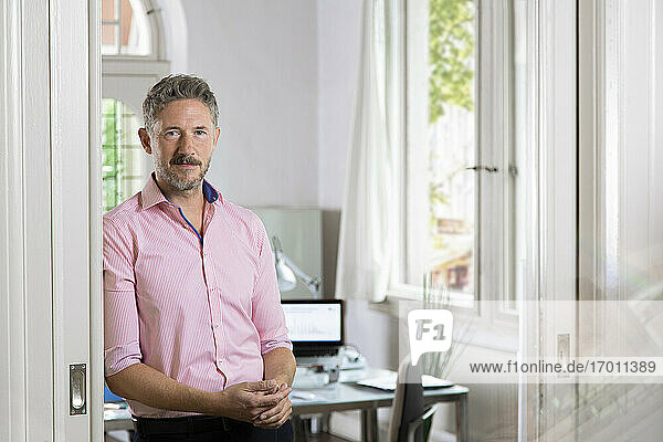 Confident businessman leaning on doorway of office