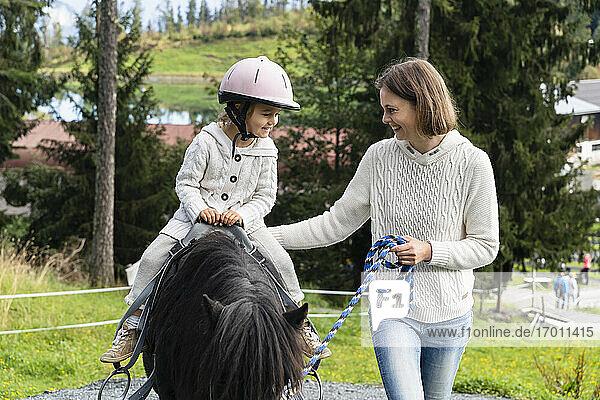 Mutter geht neben ihrer kleinen Tochter auf einem Pony spazieren