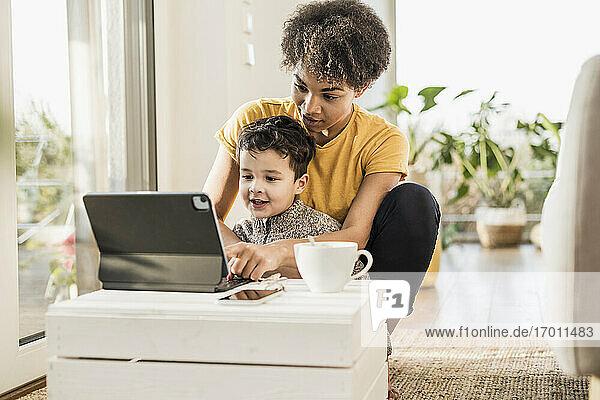 Mutter zeigt ihrem Sohn ein digitales Tablet  während sie zu Hause sitzt Mutter zeigt ihrem Sohn ein digitales Tablet, während sie zu Hause sitzt
