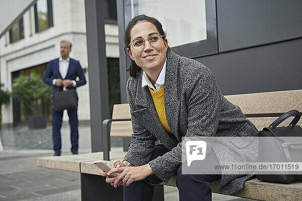Lächelnde Geschäftsfrau auf einer Bank sitzend  die an einer Bushaltestelle wartet  während ein Geschäftsmann im Hintergrund steht