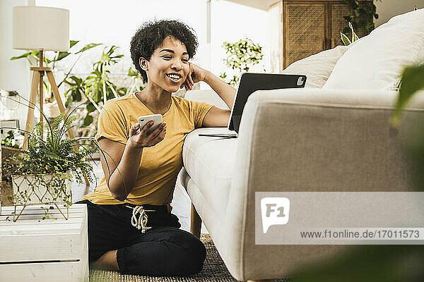 Junge Frau mit Mobiltelefon  die zu Hause sitzend auf einem digitalen Tablet spricht Junge Frau mit Mobiltelefon, die zu Hause sitzend auf einem digitalen Tablet spricht
