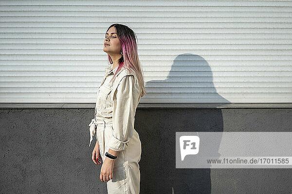 Hipster Frau mit geschlossenen Augen an der Wand an einem sonnigen Tag Hipster Frau mit geschlossenen Augen an der Wand an einem sonnigen Tag