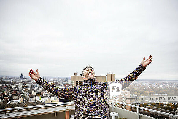 Smiling man standing with arms outstretched on rooftop