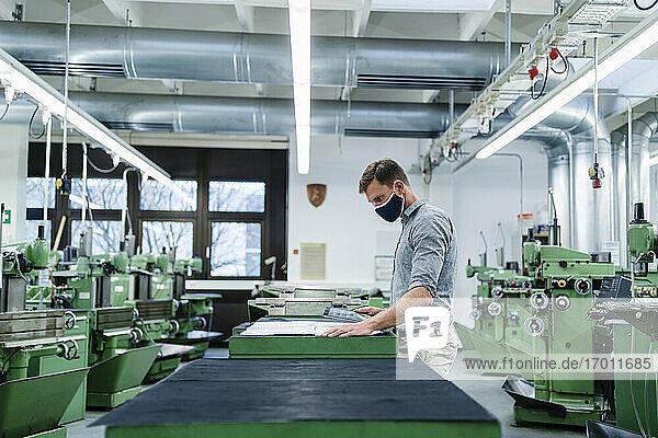 Geschäftsmann mit digitalem Tablet  der einen Bauplan in einer Fabrik während einer Pandemie prüft