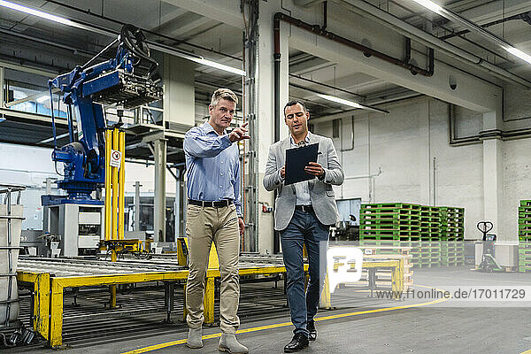 Geschäftskollegen diskutieren beim Spaziergang in der Fabrik