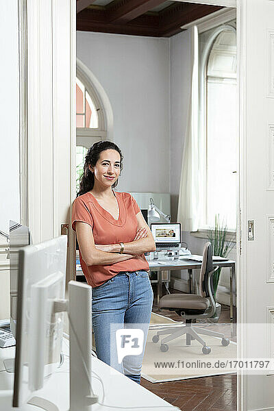 Smiling businesswoman with arms crossed on doorway in office