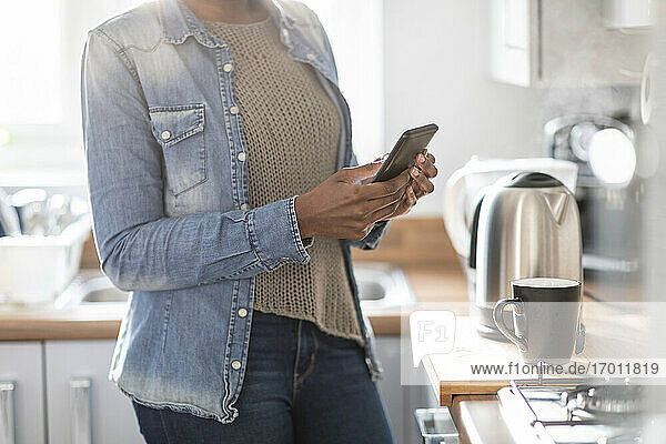 Woman using smart phone in kitchen