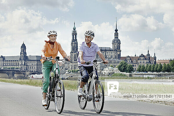 Senior couple cycling electric bicycle on road at Hausmannsturm  Dresden  Germany