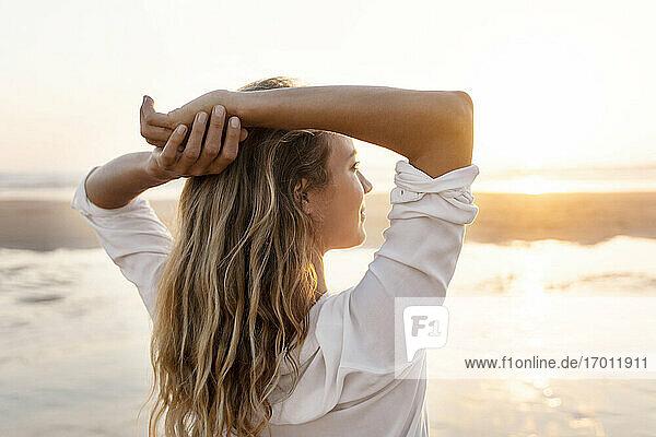 Unbekümmerte Frau mit Händen hinter dem Kopf  die die Aussicht betrachtet  während sie am Meer steht Unbekümmerte Frau mit Händen hinter dem Kopf, die die Aussicht betrachtet, während sie am Meer steht