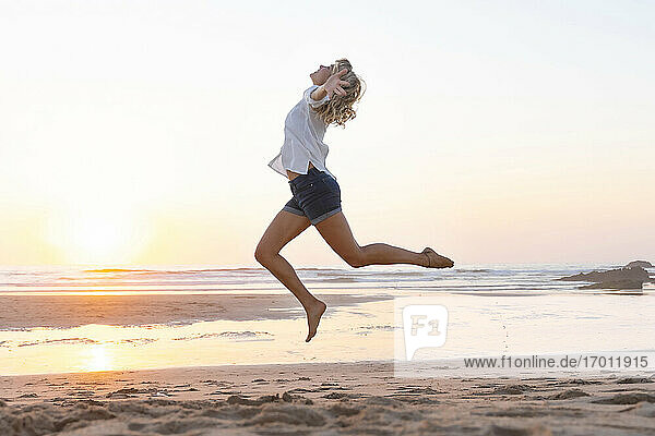 Carefree woman with arms outstretched jumping against sea during sunset