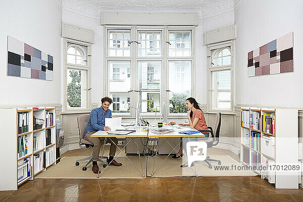 Businessman holding document with female colleague in office cabin