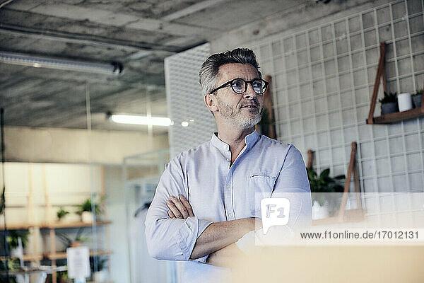 Businessman wearing eyeglasses looking away while standing with arms crossed