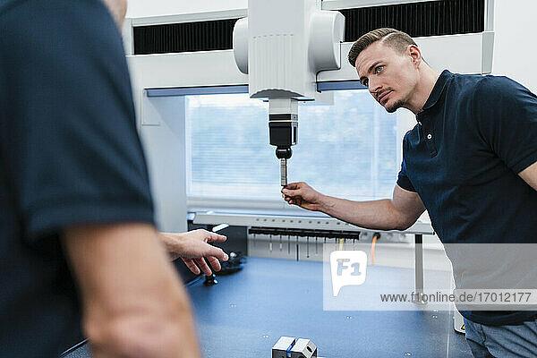 Mittlerer erwachsener Techniker und männlicher Kollege arbeiten zusammen an einer Maschine in einer Fabrik