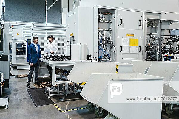 Männliche Kollegen mit Dokumentenpapier an einer Produktionsanlage in der Industrie