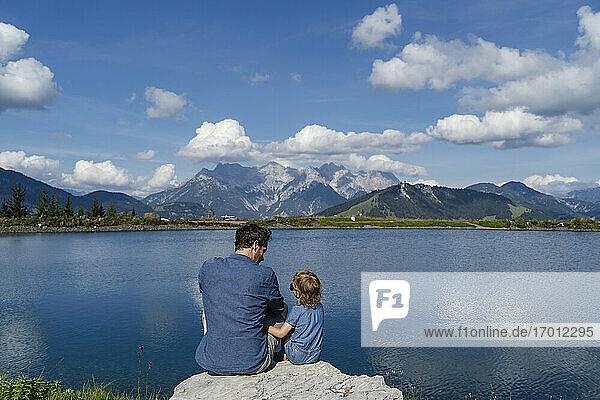 Vater und kleine Tochter sitzen zusammen auf einem Felsen am Seeufer