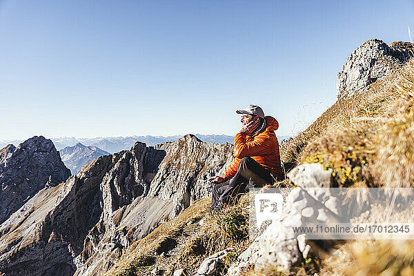 Male hiker contemplating while sitting on mountain against clear sky during sunny day