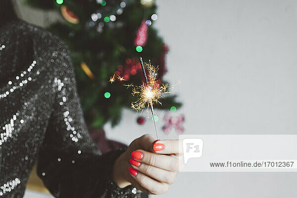 Woman holding sparkler while standing at home during Christmas