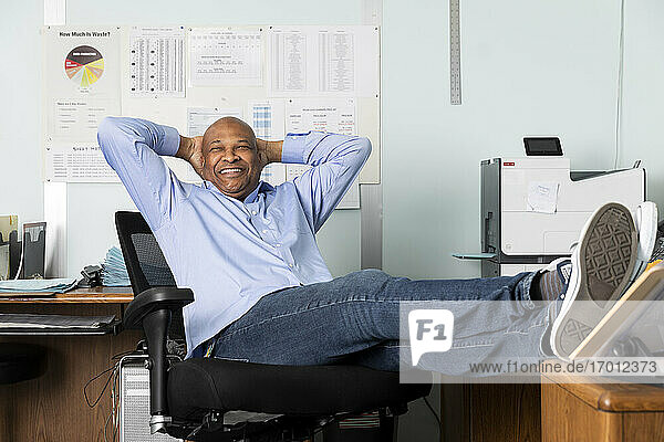 Cheerful supervisor sitting with hands behind back in print shop