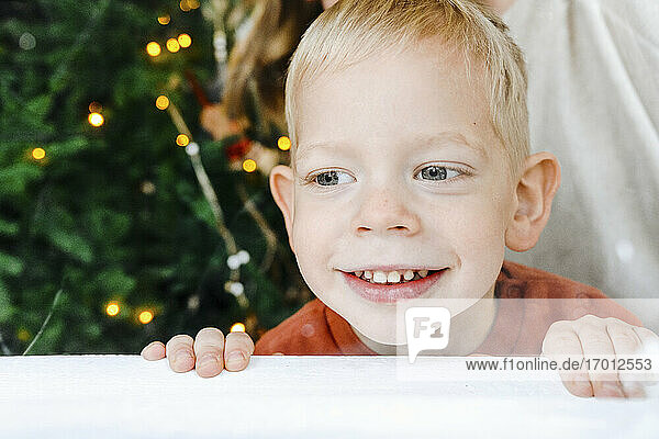 Close-up of cute smiling boy looking away at table