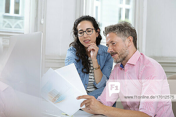 Female and male professionals discussing over document in meeting at office