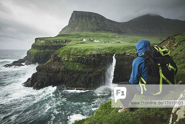 Dänemark  Färöer Inseln  Gasadalur Dorf  M-Lafossur Wasserfall  Mann mit Rucksack sitzt auf dem Rand der Klippe und schaut auf Mulafossur Wasserfall