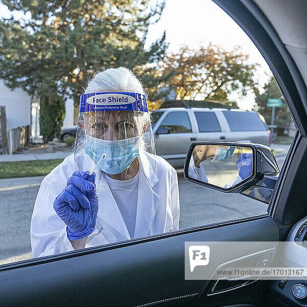 Weibliches medizinisches Personal in Schutzkleidung nähert sich Auto mit Coronavirus-Tupfer-Test