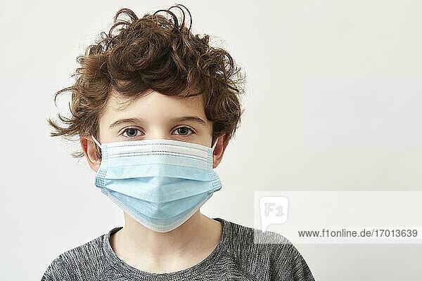 Junge (8-9) mit Gesichtsschutzmaske