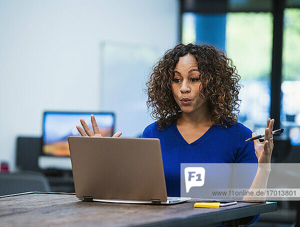 Frau schaut auf Laptop am Schreibtisch im Büro