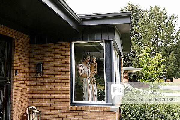 Mutter mit Baby-Sohn (18-23 Monate) stehend hinter Fenster