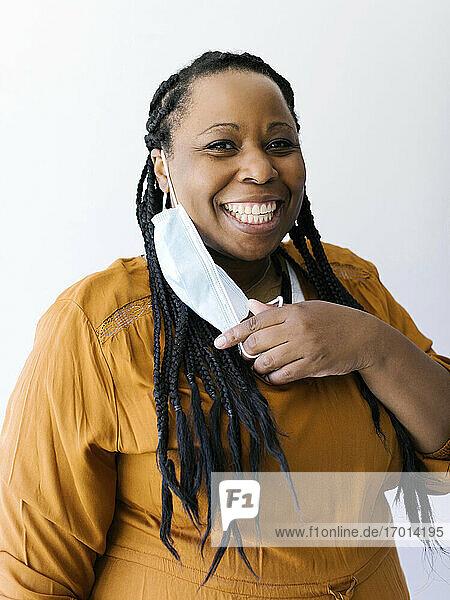Studio-Porträt einer lächelnden Frau  die eine schützende Gesichtsmaske hält