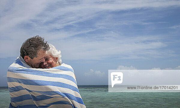Indischer Ozean  Malediven  Ari Atoll  Vilamendhoo Insel  Glückliches Paar in gestreiften Strandtuch auf tropischen Strand gewickelt